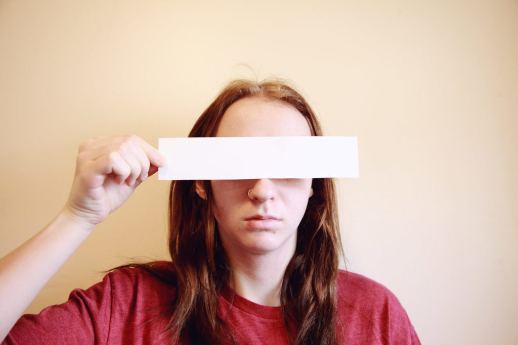 Person holding blank rectangle of paper over eyes.